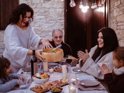 Family celebrating with lunch at traditional rustic stonebuilt cottage in Italy - Gift Boxes fresh local produce